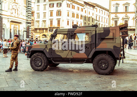 Soldiers keep watch in the square in front of the Florence Cathedral while crowds of tourists queue for entry. - Stock Photo