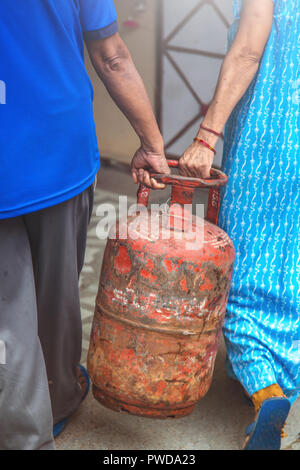 Indian man and woman carrying lpg from filling station back to their home - Stock Photo
