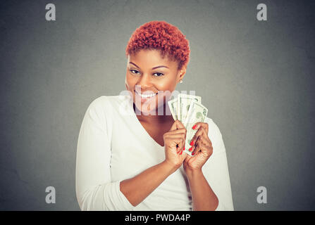 Portrait of super happy excited successful young woman holding money dollar bills in hand, isolated on gray background. Concept of financial reward