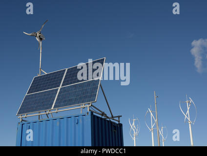 Photovoltaic array, four panel solar array on weather radar station, vertical axis wind turbines in background in car park, Cleveleys lancashire uk - Stock Photo