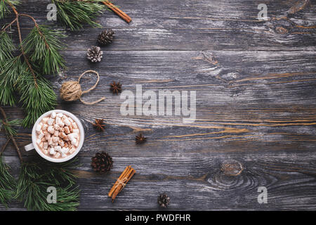 Cup of hot cocoa with marshmallows on wooden background with pine branches, pine cones, cinnamon sticks and anise stars. Traditional winter hot drink. - Stock Photo