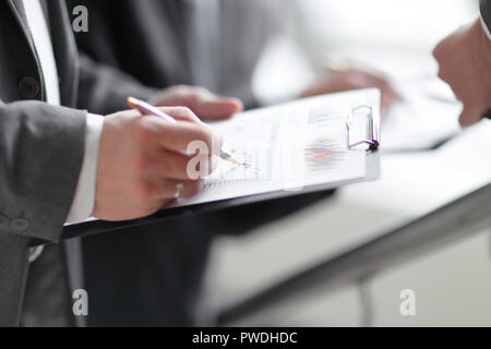 businessman at desk checking a financial report and pointing at - Stock Photo