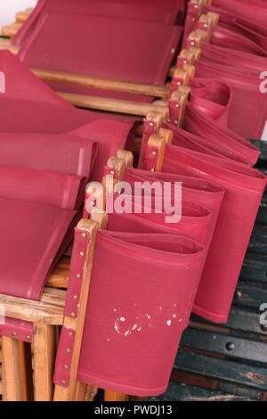 Red canvas directors chairs stacked up outside a restaurant Ciutadella Menorca Spain - Stock Photo