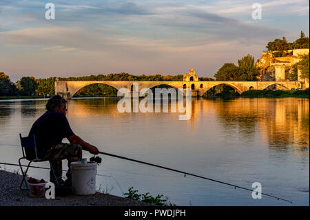 France. Vaucluse (84). Avignon. Fisherman on the banks of the Rhone, in background Pont Saint-Bénézet, commonly called Pont d'Avignon, built from 1177 - Stock Photo