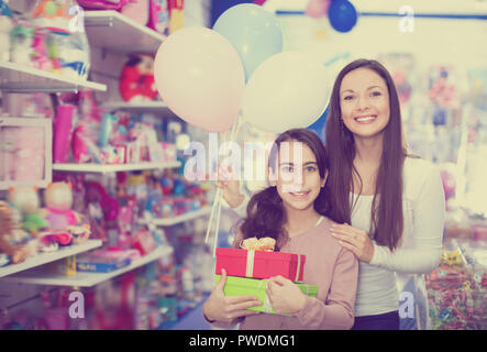 Portrait of positive mother and daughter holding gifts and balloons in store - Stock Photo