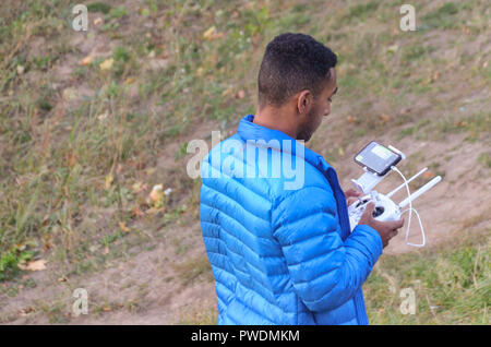 Man in blue jacket operating a drone - Stock Photo
