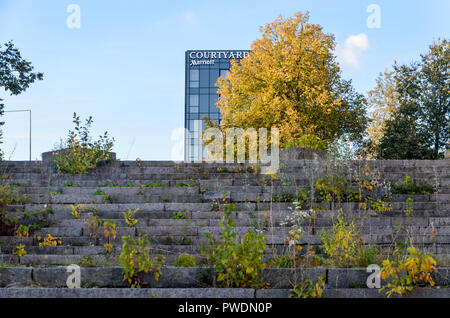 Grass growing on the staircase of the disused Vilnius Palace of Concerts and Sports, with fancy hotel in the background - Stock Photo