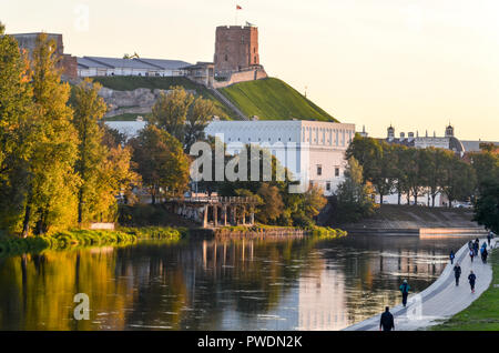 Gediminas Hill and tower castle, in Vilnius, Lithuania, by the Neris river, with people walking on the promenade - Stock Photo