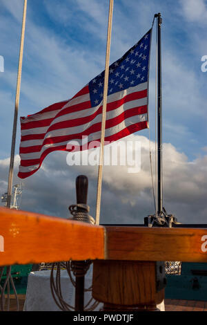 American flag flying from the stern rail of USS Constituion - Old Ironsides, in Boston Harbor, Massachusetts, USA - Stock Photo