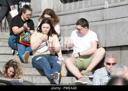 London, UK. 16th Oct, 2018. People enjoy the pleasant autumn sunshine and warm weather in Trafalgar Square at the end of Storm Callum Credit: amer ghazzal/Alamy Live News - Stock Photo