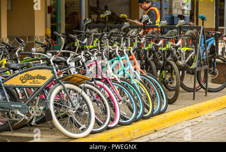 REVELSTOKE, BRITISH COLUMBIA, CANADA - JUNE 2018: Bicycles for hire lined up outside a shop in Revelstoke town centre. - Stock Photo