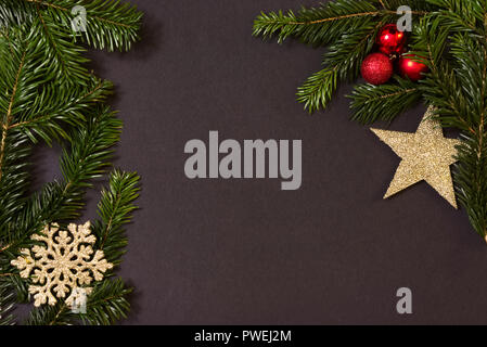 Christmas decoration on black paper with green fir branches, golden stars and little red balls, background for cards etc., top view with copy space - Stock Photo