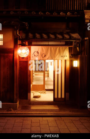 Gion Acca Japanese restaurant entrance door with a Noren curtain and a red lantern at night. Hanamikoji Dori street in Gion district. Higashiyama, Kyo - Stock Photo