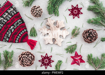 Nordic style Christmas decor. Red knitted winter hat, green pine branches, cones and stars, on concrete background. - Stock Photo