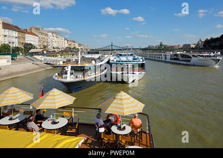Hungary, Central Hungary, Budapest, Danube, Capital City, tourism, holidays, freetime, Danube river cruise, shipping pier at the Danube bank, ahead the cruiser aROSA Mia, open afterdeck, sunshades, dishes, tourists, on the Danube the SS Maria Theresa, waterside promenade of Pest, business houses and residential buildings, Danube landscape, behind the Liberty Bridge between Pest and Buda, UNESCO World Heritage Site - Stock Photo