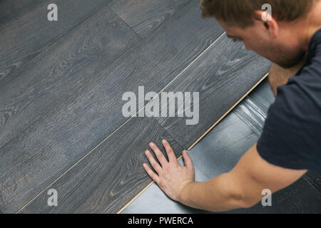 man installing laminate floor - Stock Photo