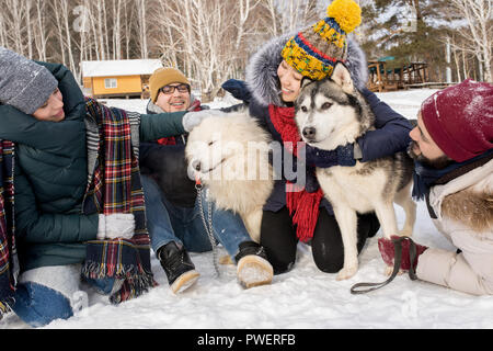 Full length portrait of  happy young people playing with two dogs outdoors in snow while enjoying time in winter resort - Stock Photo