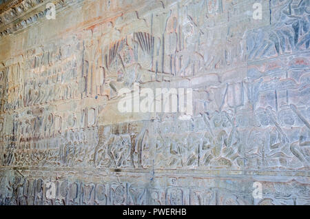 The wall of one of the galleries of Angkor Wat with its linear arrangement of stone carving, adorned with bas-reliefs showing large-scale narrative sc - Stock Photo