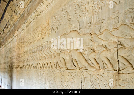 The wall of one of the galleries of Angkor Wat with its linear arrangement of stone carving, adorned with bas-reliefs showing asuras and devas - divin - Stock Photo