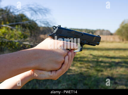 Gun in a hand. Boy shooting an air gun on a meadow. In the background colorful autumn in Poland. - Stock Photo