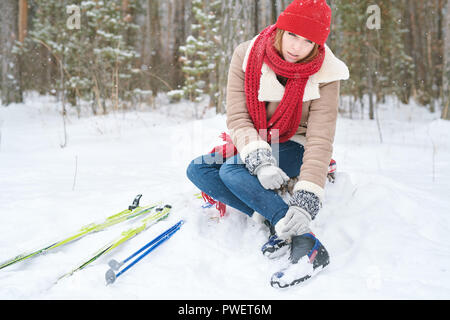 Full length portrait of beautiful young woman rubbing ankles after injury during ski walk in winter forest, copy space - Stock Photo