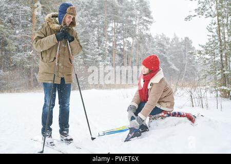 Full length portrait of active young couple skiing in winter forest focus on woman rubbing sprained ankle and looking at boyfriend, copy space - Stock Photo