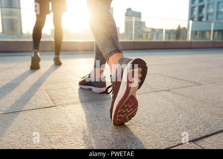 Female sneakers on woman's feet - Stock Photo