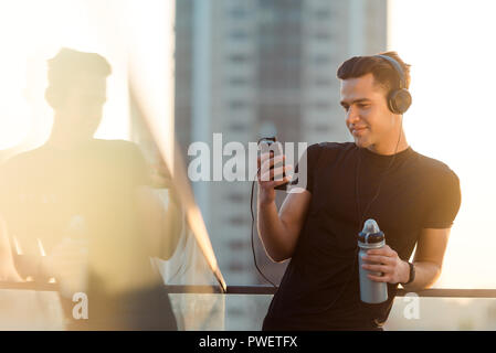 Athletic guy texting on phone - Stock Photo
