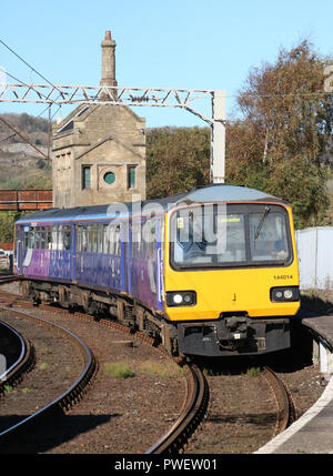 Pacer diesel multiple unit train arriving at Carnforth railway station passing a disused old midland stone signal box at the end of platform 1. - Stock Photo