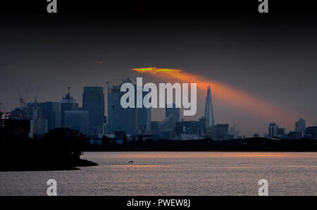 A shard of sunlight shines through the clouds over the Shard skyscraper and Canary Wharf at sunset, London, England. - Stock Photo