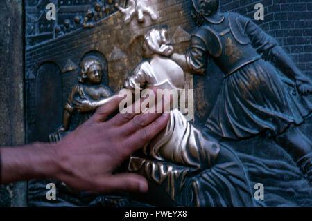 Tourists touching Bronze Wishing convex statue, bronze plaque of John of Nepomuk,  In Charles Bridge, Karlův most, Prague, Czech Republic. - Stock Photo