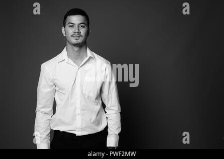 Young multi-ethnic Asian businessman against gray background in  - Stock Photo