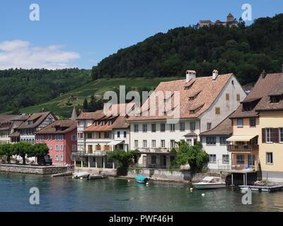 European STEIN am RHEIN town in SWITZERLAND with boats on Rhine River and Hohenklingen castle above on alpine landscape - Stock Photo
