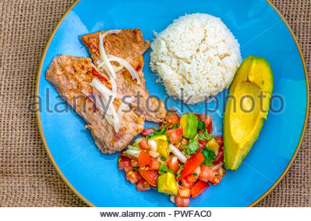 Latin American cuisine fusion: pork steak, white rice,pico de gallo and avocado.Mexican and Cuban cuisine fusion produces a healthy balanced plate of  - Stock Photo