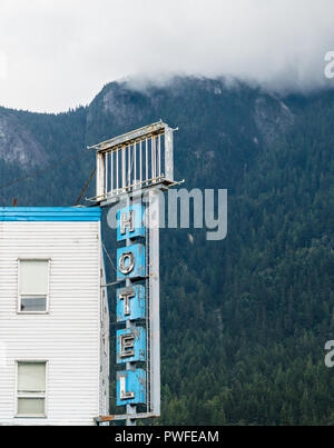 Abandoned hotel sign in downtown Hope with stormy weather over the surrounding mountains, British Columbia, Canada - Stock Photo
