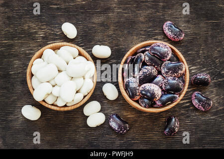 Different types of legumes - Cannellini Beans, Black and Red Kidney Beans, Lima and Pinto Beans had sorted in wooden bowls. - Stock Photo