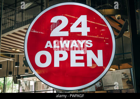 24 Hours Always Open Sign in front of the regular coffee cafe or co-working space in the city new trend of working space - Stock Photo