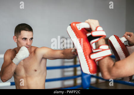 Kickboxer training with partner in boxing paws, using boxing mitts. Preparing for competition - Stock Photo