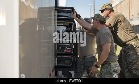 Service members from the Joint Communications Support Element and the 290th Joint Communications Support Squadron, load communication servers into a trailer before relocating to provide internet and phone capabilities to another area in need, Oct. 13, 2018, following Hurricane Michael's devastating strike, October 13, 2018. These Total Force experts can install, operate and enhance communication services and then relocate in a matter of hours, providing critical command and control whether it is for the warfighter abroad or to help our Florida family recover from the storm. (U.S. Air Force pho - Stock Photo