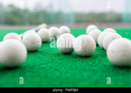 Golf balls on a synthetic grass mat at a practice range. - Stock Photo