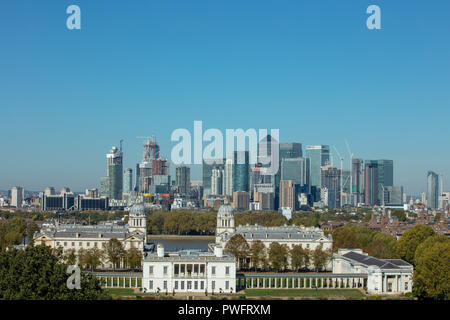View from Greenwich of tall buildings on the Isle of Dogs on the other side of the river Thames under the blue sky of a sunny and warm October midday. - Stock Photo