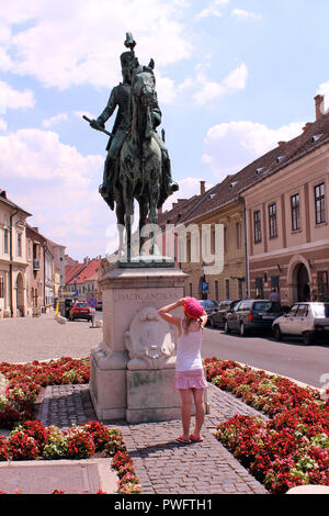 Little girl gazes up at statue of Andras Hadik mounted on a horse in Buda Castle District, Budapest, Hungary - Stock Photo