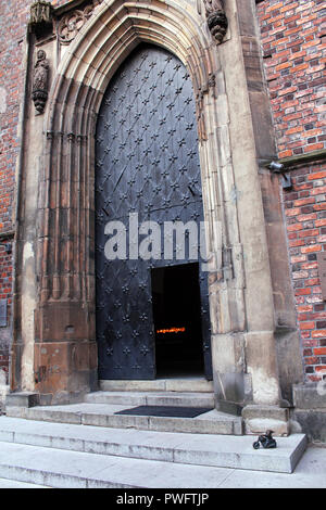 Tiny bronze statue of dwarf on motorcycle upon doorstep of St. Mary Magdalene Church, symbol of Alternative Orange movement in Wroclaw, Poland - Stock Photo