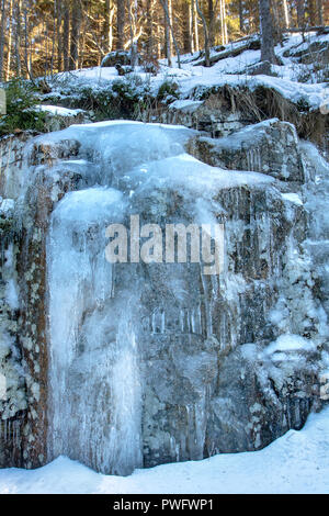 Icicle hangs from a rock in a winter nature. The water stream is froze on the stone on the rock wall. - Stock Photo