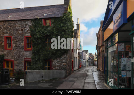 Early Sunday morning on Albert Street in Kirkwall, Orkney, Scotland, with the sun just peeking over the buildings; colorful blue sky, golden light. - Stock Photo