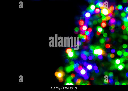 Blurred decoration of Christmas tree on dark background. Defocused part of X-mas tree with lighting bulb and decoration at night. - Stock Photo