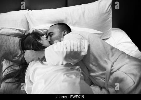 Young romantic couple relaxing and kissing in bed. Pretty girl and brunette man. Black and white photo. - Stock Photo