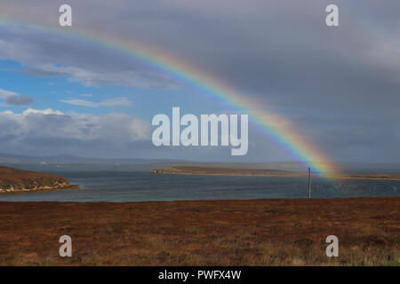 Gorgeous rainbow (double!) over Wide Firth, Orkney Mainland, Scotland, on a blustery, on and off rainy day. Blue sky, gray clouds, sea and brown field - Stock Photo