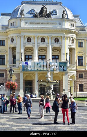 Tourists of various nationalities chatting and taking pictures in front of Slovak National Theatre in Bratislava on sunny summer day. (portrait view) - Stock Photo