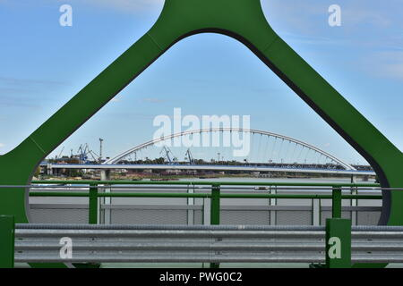 View of Apollo Bridge over river Danube through green painted steel arch of new Old Bridge. - Stock Photo